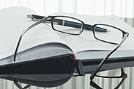 Close up of notebook, pen and spectacles with reflection on table - ASF004377