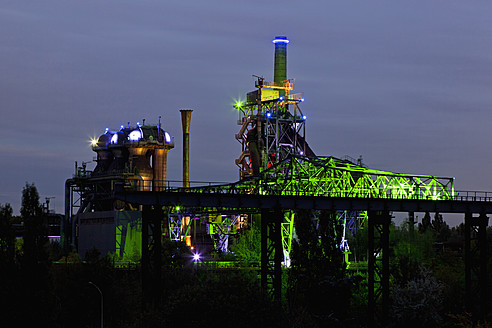 Germany, Nordrhein-Westfalen, Duisburg, Duisburg-Nord Landscape Park, View of illuminated blast furnace and smoke stacks of old industrial plant - FOF003420