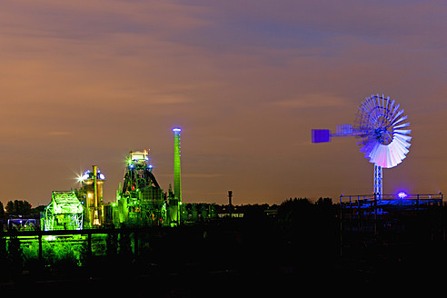 Germany, Nordrhein-Westfalen, Duisburg, Duisburg-Nord Landscape Park, View of illuminated blast furnace and wind mill of industrial plant at night - FOF003423