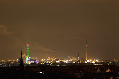 Germany, Nordrhein-Westfalen, Duisburg, View of illuminated green tower and industrial plant at night - FOF003425