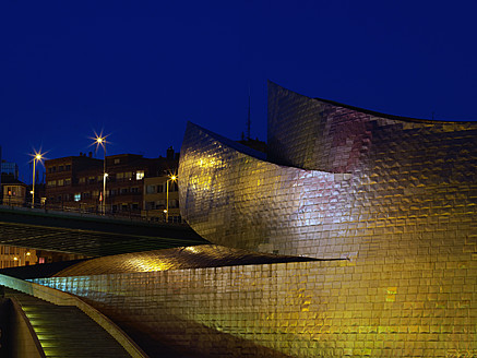 Spain, Basque country, Bilbao, View of Guggenheim Museum Bilbao with bridge in background at night - BSC000017