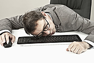 Close up of mature businessman lying on keyboard at office - MAEF003444