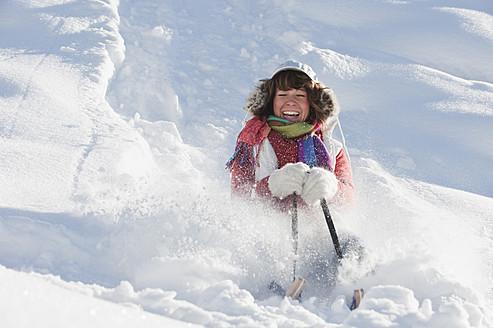 Austria, Salzburg Country, Flachau, Young woman riding on sledge in snow - HHF003692