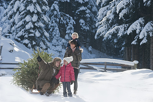 Austria, Salzburg Country, Flachau, View of family with christmas tree and sledge in snow - HHF003733