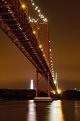 Europe, Portugal, Lisbon, View of suspension bridge with river Tagus at night - FOF003438