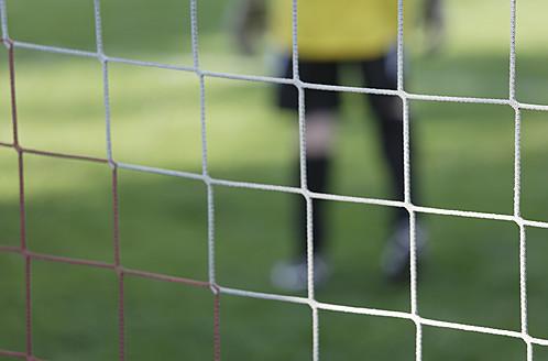 Germany, Bavaria, Schaeftlarn, Close up of football net with teenage boy goalkeeper in background - TCF001607