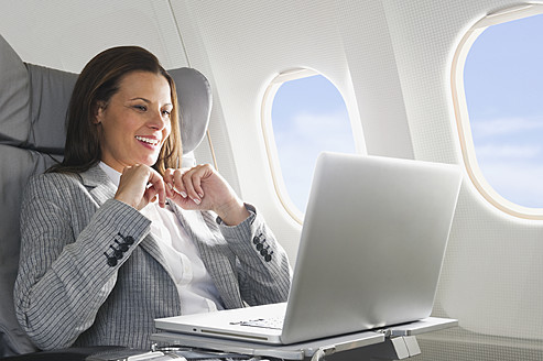 Germany, Bavaria, Munich, Mid adult businesswoman using laptop in business class airplane cabin - WESTF016802