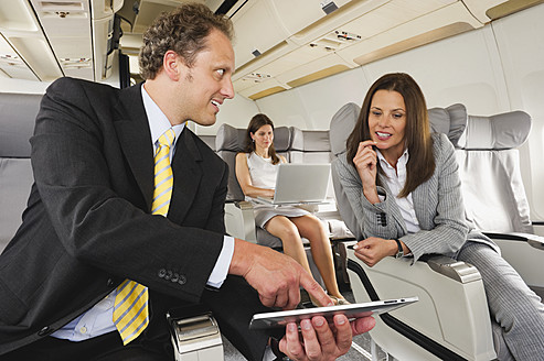Germany, Bavaria, Munich, Business people working on ipad and laptop in business class airplane cabin, smiling - WESTF016852