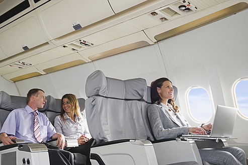 Germany, Bavaria, Munich, Business people talking and using laptop in business class airplane cabin, smiling - WESTF016857