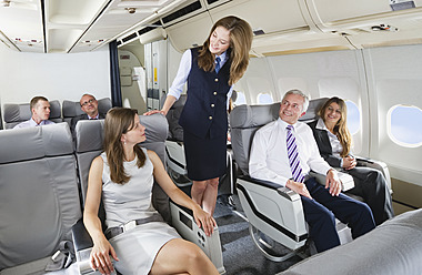 Germany, Bavaria, Munich, Stewardess and passengers in business class airplane cabin, smiling - WESTF016873