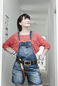 Germany, Cologne, Young woman with hammer renovating apartment - FMKF000249