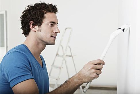 Germany, Cologne, Close up of young man painting in renovating apartment - FMKF000327