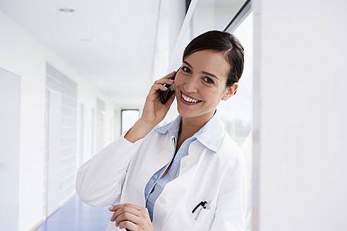 Germany, Bavaria, Diessen am Ammersee, Young doctor talking on mobile phone and leaning, smiling - JRF000247