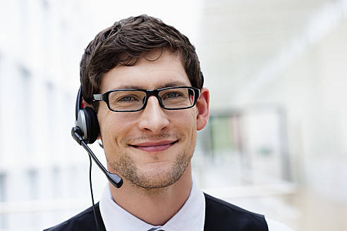 Germany, Bavaria, Diessen am Ammersee, Close up of businesssman with headset, smiling, portrait - JRF000269