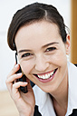 Germany, Bavaria, Diessen am Ammersee, Close up of young businesswoman talking on mobile phone, smiling, portrait - JRF000288