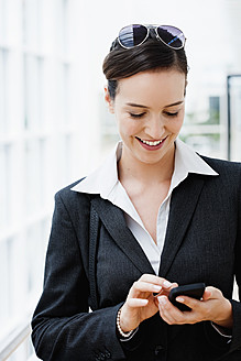 Germany, Bavaria, Diessen am Ammersee, Young businesswoman using mobile phone, smiling - JRF000290
