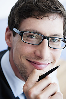 Germany, Bavaria, Diessen am Ammersee, Close up of businessman in thick spectacles holding pen, smiling, portrait - JRF000318