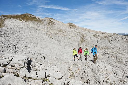 Austria, Kleinwalsertal, Group of people hiking on rocky mountain trail - MIRF000218