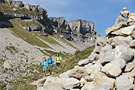 Austria, Kleinwalsertal, Group of people hiking on mountain trail with stack of stones in foreground - MIRF000224