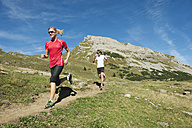 Austria, Kleinwalsertal, Man and woman running on mountain trail - MIRF000233