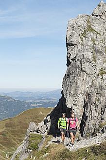 Austria, Kleinwalsertal, Man and woman hiking near rocks on mountain - MIRF000239