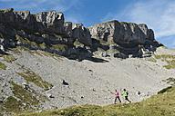 Austria, Kleinwalsertal, Man and woman hiking on mountain trail - MIRF000242