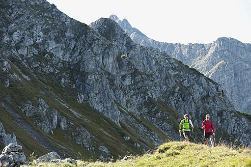Austria, Kleinwalsertal, Man and woman hiking on mountain trail - MIRF000248