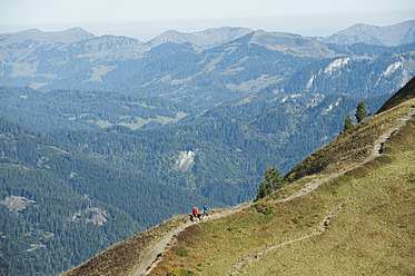 Austria, Kleinwalsertal, Man and woman hiking on mountain trail - MIRF000251
