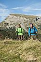 Austria, Kleinwalsertal, Man and woman hiking on mountain trail, smiling - MIRF000254