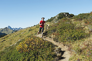 Austria, Kleinwalsertal, Mid adult man running on mountain trail - MIRF000257