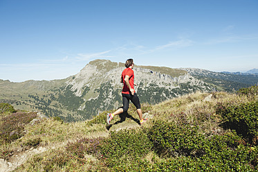 Austria, Kleinwalsertal, Mid adult man running on mountain trail - MIRF000263