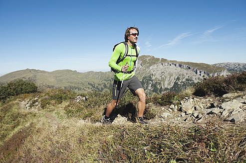 Austria, Kleinwalsertal, Mid adult man hiking on mountain trail - MIRF000266