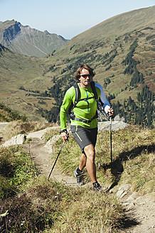 Austria, Kleinwalsertal, Mid adult man hiking on mountain trail - MIRF000269