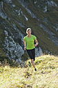 Austria, Kleinwalsertal, Young woman running on mountain trail - MIRF000272