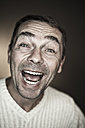 Close up of mature man making funny faces against black background, laughing, portrait - MAEF003550