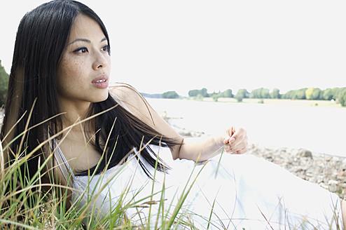 Germany, Young woman lying near grass at Rhine riverside - LFO000061