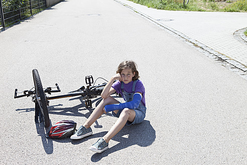 Germany, Bavaria, Wounded girl sitting on road after bicycle accident - MAEF003588