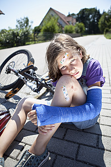 Germany, Bavaria, Wounded girl sitting on road after bicycle accident - MAEF003577
