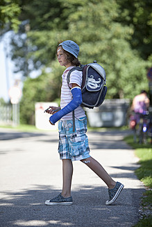 Germany, Bavaria, Wounded girl with arm in cast on way to school - MAEF003584