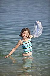 Germany, Bavaria, Broken arm of girl in cast covered with plastic bag, smiling - MAEF003587