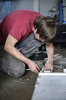 Germany, Ebenhausen, Mechatronic technician working in car garage - TCF001610