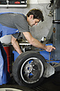 Germany, Ebenhausen, Mechatronic technician working on tyre in car garage - TCF001618