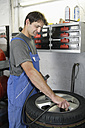 Germany, Ebenhausen, Mechatronic technician working on tyre in car garage - TCF001621