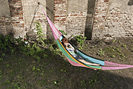 Germany, Berlin, Young woman in hammock using cell phone, smiling - WESTF016901