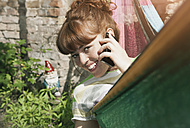 Germany, Berlin, Young woman in hammock using cell phone, smiling, portrait - WESTF016904
