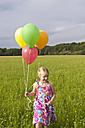 Germany, North Rhine-Westphalia, Hennef, Girl holding balloons and running through meadow - KJF000127