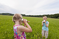 Germany, North Rhine-Westphalia, Hennef, Boy and girl in meadow playing with tin can phone - KJF000134
