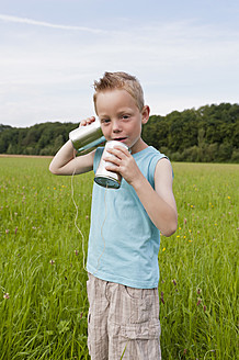 Germany, North Rhine-Westphalia, Hennef, Boy standing in meadow and playing with tin can phone - KJF000137