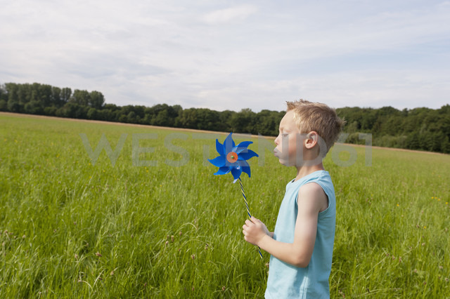 Germany, North Rhine-Westphalia, Hennef, Boy blowing wind mill in meadow - KJF000140