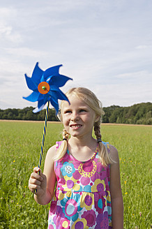 Germany, North Rhine-Westphalia, Hennef, Girl standing with wind mill in meadow - KJF000144